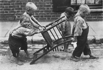 Children in Deptford playing with a chair  (https://it.pinterest.com/pin/409123947385170658/)